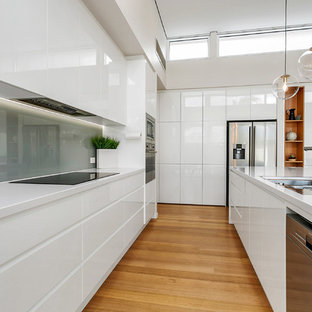 Contemporary u-shaped kitchen in Adelaide with flat-panel cabinets, white cabinets, grey splashback, glass sheet splashback, stainless steel appliances, medium hardwood floors, with island, brown floor and white benchtop.
