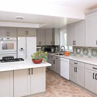 Идея дизайна: маленькая угловая кухня в классическом стиле с обеденным столом, накладной раковиной, фасадами в стиле шейкер, серыми фасадами, столешницей из кварцевого композита, синим фартуком, фартуком из цементной плитки, белой техникой, полом из керамической плитки и розовым полом без острова