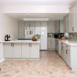 Cette photo montre une petite cuisine américaine chic en L avec un évier posé, un placard à porte shaker, des portes de placard grises, un plan de travail en quartz modifié, une crédence bleue, une crédence en carreau de ciment, un électroménager blanc, un sol en carrelage de céramique, aucun îlot et un sol rose.