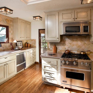 Mediterranean enclosed kitchen designs - Tuscan enclosed kitchen photo in San Diego with an undermount sink, recessed-panel cabinets, beige cabinets, beige backsplash and stainless steel appliances
