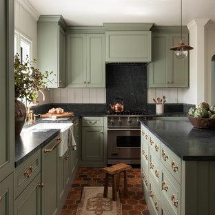 Bild på ett vintage svart svart l-kök, med en rustik diskho, luckor med infälld panel, gröna skåp, svart stänkskydd, en köksö och rött golv