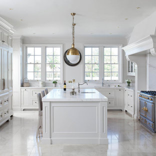 This is an example of a large traditional u-shaped open plan kitchen in Other with a drop-in sink, beaded inset cabinets, white cabinets, marble benchtops, white splashback, marble splashback, stainless steel appliances, porcelain floors, with island, beige floor and yellow benchtop.