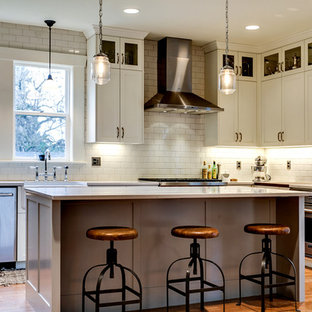 Mid-sized industrial l-shaped eat-in kitchen in Portland with a farmhouse sink, shaker cabinets, white cabinets, quartz benchtops, white splashback, ceramic splashback, stainless steel appliances, medium hardwood floors, with island and brown floor.