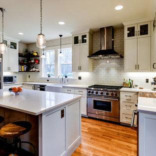 ポートランドの中サイズのインダストリアルスタイルのおしゃれなキッチン (エプロンフロントシンク、シェーカースタイル扉のキャビネット、白いキャビネット、クオーツストーンカウンター、白いキッチンパネル、セラミックタイルのキッチンパネル、シルバーの調理設備の、無垢フローリング、茶色い床) の写真