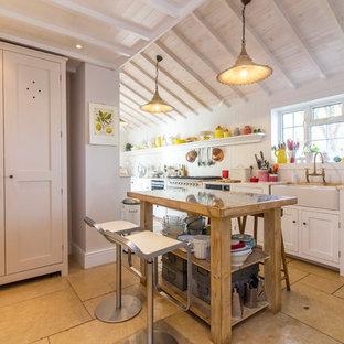 Modelo de cocina lineal, de estilo de casa de campo, de tamaño medio, con fregadero sobremueble, armarios con paneles empotrados, puertas de armario blancas, encimera de madera, una isla y suelo beige