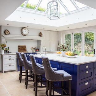 Photo of a traditional kitchen in Gloucestershire with shaker cabinets, grey cabinets, grey splashback, coloured appliances, an island, beige floors and white worktops.