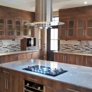 他の地域の広いカントリー風おしゃれなキッチン (ドロップインシンク、フラットパネル扉のキャビネット、濃色木目調キャビネット、御影石カウンター、マルチカラーのキッチンパネル、モザイクタイルのキッチンパネル、シルバーの調理設備、クッションフロア、黄色い床、マルチカラーのキッチンカウンター) の写真
