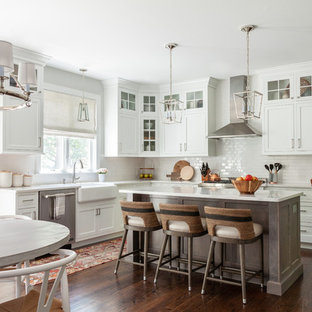 Example of a transitional medium tone wood floor open concept kitchen design in New York with a farmhouse sink, shaker cabinets, white cabinets, quartz countertops, white backsplash, ceramic backsplash, stainless steel appliances, an island and white countertops