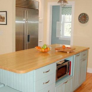 Imagen de cocina costera, pequeña, con fregadero bajoencimera, armarios con paneles empotrados, puertas de armario turquesas, encimera de madera, electrodomésticos de acero inoxidable, suelo de madera clara y una isla