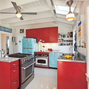 Cette photo montre une cuisine bord de mer en L avec un placard à porte plane, des portes de placard rouges, un plan de travail en inox et un électroménager de couleur.