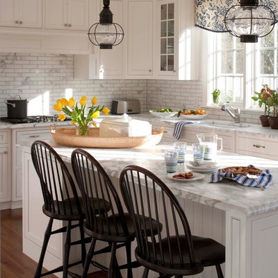 Eat-in kitchen - mid-sized traditional l-shaped dark wood floor eat-in kitchen idea in Boston with marble countertops, an undermount sink, shaker cabinets, white cabinets, white backsplash, stainless steel appliances and an island
