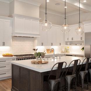 サンフランシスコの中サイズのカントリー風おしゃれなキッチン (エプロンフロントシンク、白いキャビネット、クオーツストーンカウンター、白いキッチンパネル、サブウェイタイルのキッチンパネル、シルバーの調理設備の、白いキッチンカウンター、シェーカースタイル扉のキャビネット、無垢フローリング、茶色い床) の写真