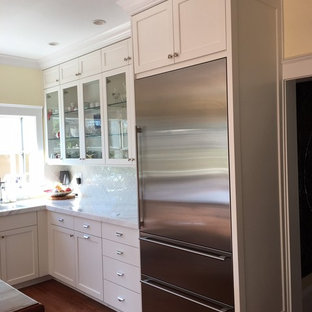 Inspiration for a mid-sized transitional l-shaped medium tone wood floor and brown floor enclosed kitchen remodel in San Francisco with shaker cabinets, white cabinets, stainless steel appliances, an island, quartz countertops, white backsplash, glass tile backsplash and white countertops