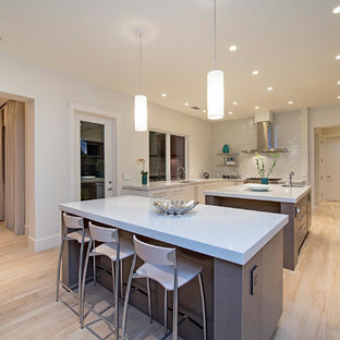 Design ideas for a large transitional u-shaped eat-in kitchen in Miami with an undermount sink, flat-panel cabinets, grey cabinets, quartz benchtops, white splashback, porcelain floors, multiple islands and stainless steel appliances.