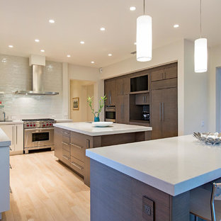 Large contemporary eat-in kitchen photos - Example of a large trendy u-shaped porcelain floor eat-in kitchen design in Miami with an undermount sink, flat-panel cabinets, gray cabinets, quartz countertops, white backsplash, glass sheet backsplash, paneled appliances and two islands