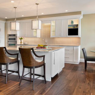 Transitional galley medium tone wood floor open concept kitchen photo in Miami with an undermount sink, shaker cabinets, white cabinets, beige backsplash, stainless steel appliances and an island