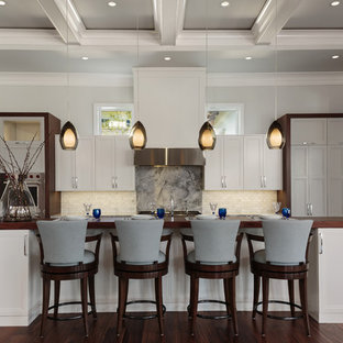 Inspiration for a large transitional galley brown floor and dark wood floor kitchen remodel in Miami with white cabinets, stainless steel appliances, an island, recessed-panel cabinets, wood countertops, beige backsplash, subway tile backsplash and brown countertops