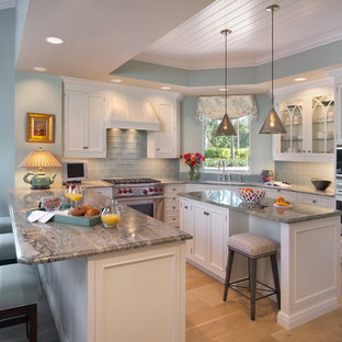 Photo of a large beach style u-shaped eat-in kitchen in Miami with an undermount sink, recessed-panel cabinets, white cabinets, granite benchtops, blue splashback, glass tile splashback, stainless steel appliances, light hardwood floors and with island.