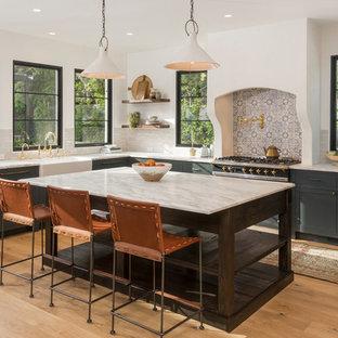 ロサンゼルスの地中海スタイルのおしゃれなキッチン (シェーカースタイル扉のキャビネット、エプロンフロントシンク、マルチカラーのキッチンパネル、黒い調理設備、淡色無垢フローリング、マルチカラーのキッチンカウンター、緑のキャビネット) の写真