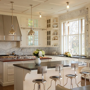 Photo of a traditional kitchen in Los Angeles with recessed-panel cabinets, beige cabinets, grey splashback, multiple islands and marble splashback.