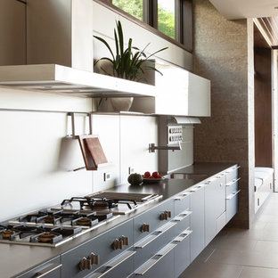 Design ideas for a large contemporary single-wall eat-in kitchen in Los Angeles with flat-panel cabinets, grey cabinets, an undermount sink, stainless steel benchtops, metallic splashback, metal splashback, panelled appliances, porcelain floors and grey floor.