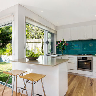 This is an example of a contemporary u-shaped kitchen in Sydney with flat-panel cabinets, white cabinets, blue splashback, glass sheet splashback, stainless steel appliances, medium hardwood floors, a peninsula, brown floor and beige benchtop.