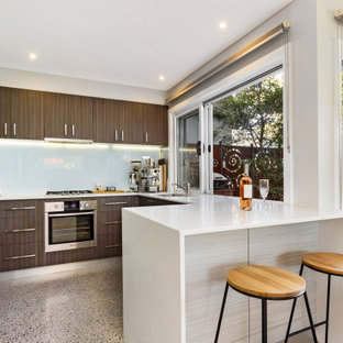 Photo of a contemporary u-shaped open plan kitchen in Sydney with brown cabinets, quartz benchtops, white splashback, porcelain splashback, stainless steel appliances, terrazzo floors, grey floor, white benchtop, an undermount sink, flat-panel cabinets and a peninsula.