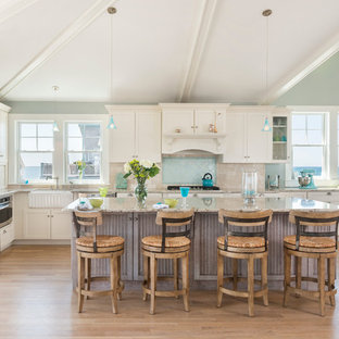 Large beach style kitchen photos - Kitchen - large beach style l-shaped light wood floor kitchen idea in Providence with a farmhouse sink, white cabinets, granite countertops, blue backsplash, stainless steel appliances, an island, shaker cabinets and glass tile backsplash