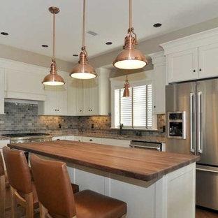 プロビデンスの中サイズのトランジショナルスタイルのおしゃれなキッチン (落し込みパネル扉のキャビネット、白いキャビネット、シルバーの調理設備の、アンダーカウンターシンク、御影石カウンター、マルチカラーのキッチンパネル、レンガのキッチンパネル、濃色無垢フローリング) の写真