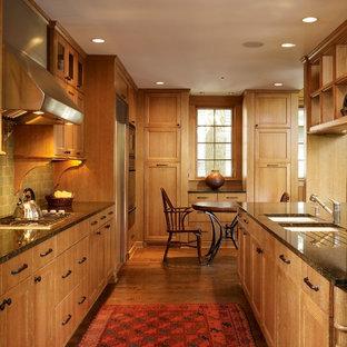 Inredning av ett modernt stort kök, med luckor med infälld panel, skåp i mellenmörkt trä, en dubbel diskho, granitbänkskiva, grönt stänkskydd, rostfria vitvaror, mellanmörkt trägolv, en köksö och stänkskydd i terrakottakakel