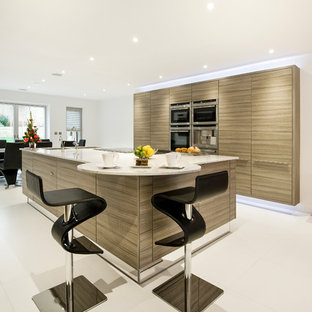 This is an example of a medium sized contemporary galley kitchen/diner in West Midlands with flat-panel cabinets, medium wood cabinets, integrated appliances and an island.