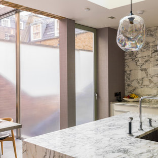 Mid-sized traditional u-shaped open plan kitchen in London with a drop-in sink, louvered cabinets, beige cabinets, marble benchtops, white splashback, marble splashback, limestone floors, with island and beige floor.