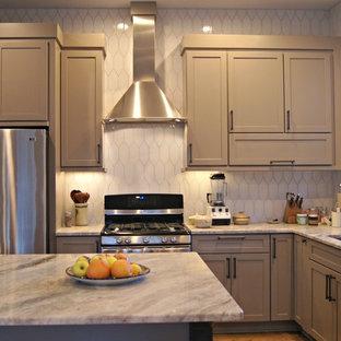 Idee per una cucina tradizionale di medie dimensioni con lavello a vasca singola, ante con riquadro incassato, ante marroni, paraspruzzi bianco, paraspruzzi in gres porcellanato, elettrodomestici in acciaio inossidabile, pavimento in legno massello medio e isola