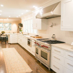This is an example of a large classic galley kitchen/diner in Nashville with a submerged sink, shaker cabinets, white cabinets, granite worktops, white splashback, ceramic splashback, stainless steel appliances, medium hardwood flooring and no island.