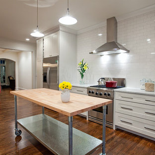 Large trendy galley medium tone wood floor kitchen photo in New York with stainless steel appliances, an undermount sink, shaker cabinets, white cabinets, marble countertops, white backsplash and an island