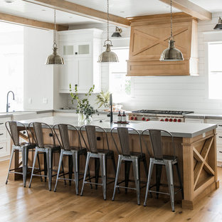 Large farmhouse eat-in kitchen photos - Inspiration for a large country medium tone wood floor and beige floor eat-in kitchen remodel in Salt Lake City with quartz countertops, a farmhouse sink, shaker cabinets, white cabinets, white backsplash, wood backsplash and an island