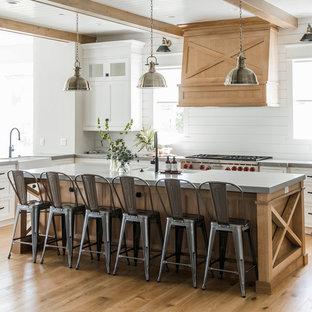 Große Country Wohnküche mit Quarzwerkstein-Arbeitsplatte, Landhausspüle, Schrankfronten im Shaker-Stil, weißen Schränken, Küchenrückwand in Weiß, Rückwand aus Holz, braunem Holzboden, Kücheninsel und beigem Boden in Salt Lake City