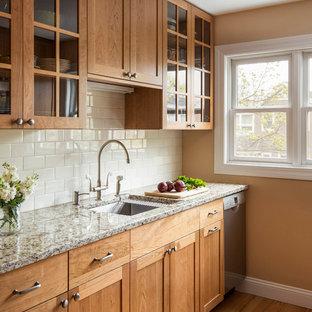 ボストンの小さいトラディショナルスタイルのおしゃれなキッチン (アンダーカウンターシンク、シェーカースタイル扉のキャビネット、淡色木目調キャビネット、御影石カウンター、黄色いキッチンパネル、サブウェイタイルのキッチンパネル、シルバーの調理設備、淡色無垢フローリング、ベージュのキッチンカウンター) の写真