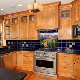 This is an example of an arts and crafts u-shaped eat-in kitchen in Denver with a drop-in sink, flat-panel cabinets, medium wood cabinets, limestone benchtops, black splashback, glass tile splashback, stainless steel appliances, medium hardwood floors and with island.