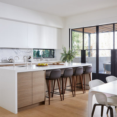 Inspiration for a modern galley medium tone wood floor and brown floor kitchen remodel in San Francisco with flat-panel cabinets, white cabinets, white backsplash, paneled appliances, an island and white countertops