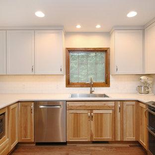 グランドラピッズの中サイズのトランジショナルスタイルのおしゃれなキッチン (シェーカースタイル扉のキャビネット、白いキャビネット、ラミネートカウンター、白いキッチンパネル、サブウェイタイルのキッチンパネル、シルバーの調理設備の、クッションフロア) の写真