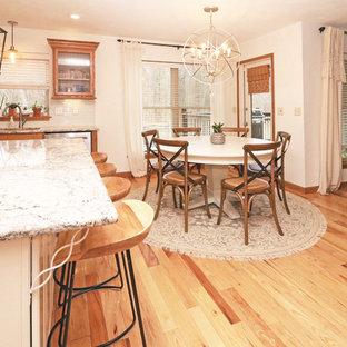 他の地域の中サイズのシャビーシック調のおしゃれなキッチン (ドロップインシンク、フラットパネル扉のキャビネット、中間色木目調キャビネット、御影石カウンター、白いキッチンパネル、サブウェイタイルのキッチンパネル、シルバーの調理設備の、淡色無垢フローリング、黄色い床、マルチカラーのキッチンカウンター) の写真