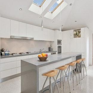 Bild på ett mellanstort funkis grå grått kök, med en dubbel diskho, luckor med upphöjd panel, vita skåp, bänkskiva i terrazo, beige stänkskydd, stänkskydd i sten, rostfria vitvaror, terrazzogolv, en köksö och grått golv