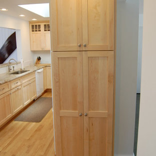 Inspiration for a mid-sized craftsman galley medium tone wood floor enclosed kitchen remodel in Burlington with an undermount sink, shaker cabinets, light wood cabinets, granite countertops, white backsplash, ceramic backsplash, white appliances and no island