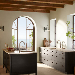 Design ideas for a large beach style u-shaped eat-in kitchen in Milwaukee with a single-bowl sink, flat-panel cabinets, dark wood cabinets, limestone benchtops, stainless steel appliances, terra-cotta floors, with island, beige splashback and beige floor.