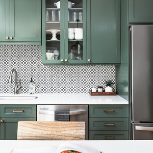Mid-sized transitional u-shaped separate kitchen in Chicago with an undermount sink, shaker cabinets, green cabinets, quartz benchtops, white splashback, cement tile splashback, stainless steel appliances, light hardwood floors, with island and white benchtop.