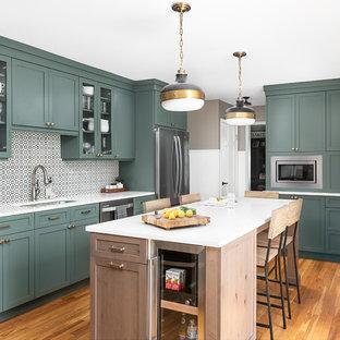 シカゴの中サイズのトランジショナルスタイルのおしゃれなキッチン (アンダーカウンターシンク、シェーカースタイル扉のキャビネット、緑のキャビネット、クオーツストーンカウンター、白いキッチンパネル、セメントタイルのキッチンパネル、シルバーの調理設備の、淡色無垢フローリング、白いキッチンカウンター) の写真