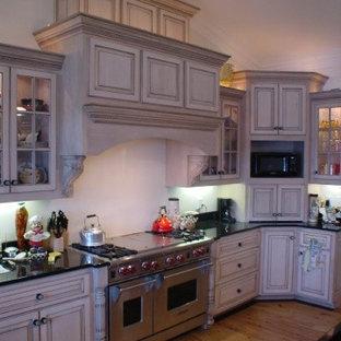 Modelo de cocina en L, tradicional, de tamaño medio, abierta, con armarios con paneles con relieve, puertas de armario beige, encimera de granito, electrodomésticos de acero inoxidable, suelo de madera clara y una isla