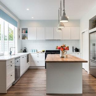 クライストチャーチの中サイズのトランジショナルスタイルのおしゃれなキッチン (アンダーカウンターシンク、シェーカースタイル扉のキャビネット、白いキャビネット、タイルカウンター、白いキッチンパネル、サブウェイタイルのキッチンパネル、黒い調理設備、ラミネートの床、茶色い床) の写真