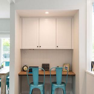 クライストチャーチの中くらいのトランジショナルスタイルのおしゃれなキッチン (アンダーカウンターシンク、シェーカースタイル扉のキャビネット、白いキャビネット、タイルカウンター、白いキッチンパネル、サブウェイタイルのキッチンパネル、黒い調理設備、ラミネートの床、茶色い床) の写真